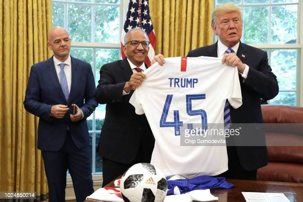 S President Donald Trump holds a US Soccer uniform as he poses for a photograph with US Soccer President Carlos Cordeiro and FIFA President Gianni...