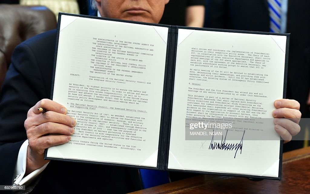US President Donald Trump holds an executive action on the organization of the National Security Council and Homeland Security Council after signing it in the Oval Office of the White House on January 28, 2017, in Washington, DC. / AFP / MANDEL