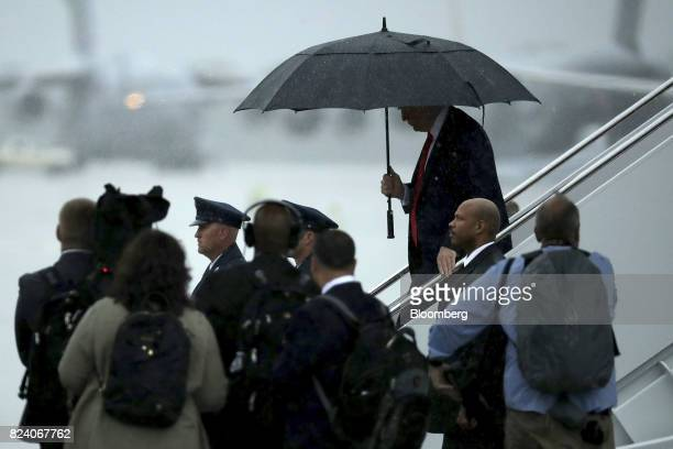 US President Donald Trump holds an umbrella after stepping out of Air Force One in Joint Base Andrews Maryland US on Friday July 28 2017 Trump...