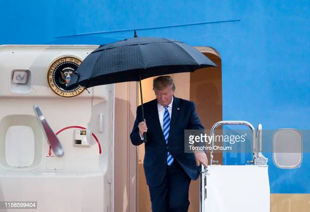 President Donald Trump holds an umbrella as he arrives at the Osaka International Airport for the G-20 Summit on June 27, 2019 in Osaka, Japan. Trump...