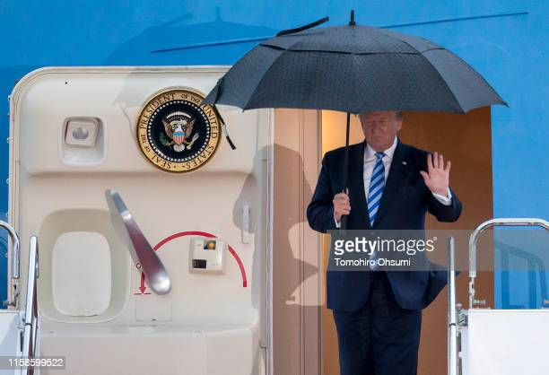 S President Donald Trump holds an umbrella as he arrives at the Osaka International Airport for the G20 Summit on June 27 2019 in Osaka Japan Trump...
