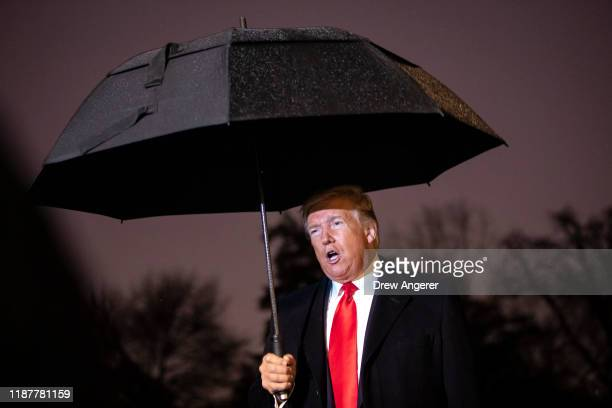 S President Donald Trump holds an umbrella as he speaks to journalists before boarding Marine One on the South Lawn of the White House on December 10...