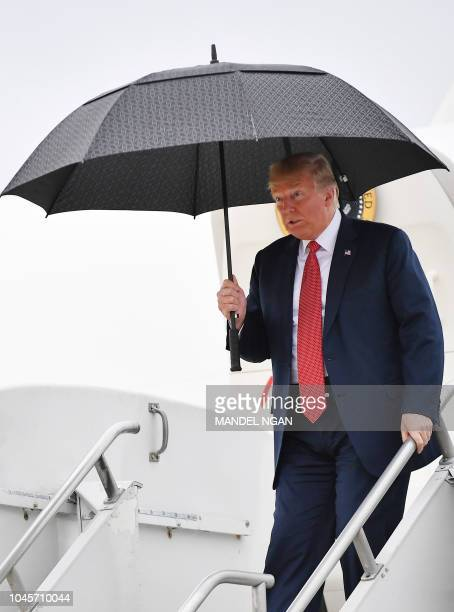 US President Donald Trump holds an umbrella as he steps off Air Force One upon arrival at Rochester International Airport in Rochester Minnesota on...