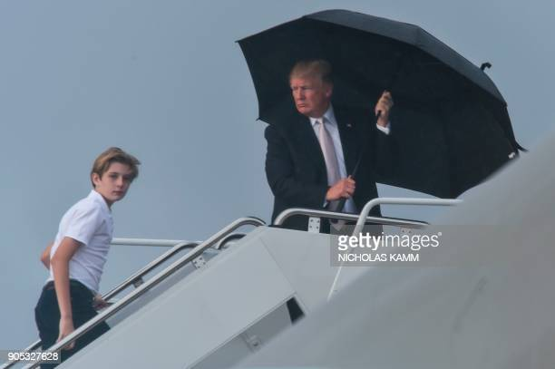 US President Donald Trump holds an umbrella as he waits for his son Barron and wife Melania to board Air Force One at Palm Beach International...