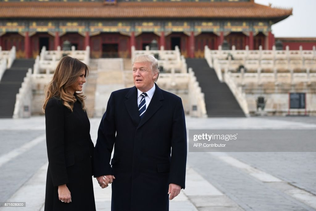 President Donald Trump holds hands with First Lady Melania Trump in the Forbidden City in Beijing on November 8, 2017. US President Donald Trump arrived in Beijing on November 8 for the critical leg of his Asia tour to drum up an uncompromising, global front against the nuclear weapons ambitions of the 'cruel dictatorship' in North Korea. / AFP PHOTO / Jim WATSON