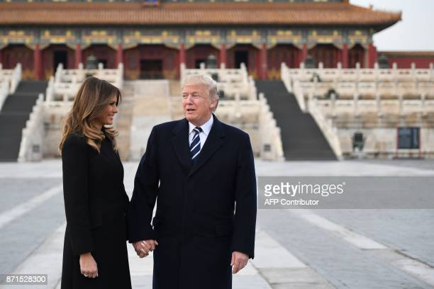 President Donald Trump holds hands with First Lady Melania Trump in the Forbidden City in Beijing on November 8 2017 US President Donald Trump...