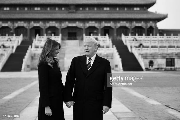 US President Donald Trump holds hands with First Lady Melania Trump in the Forbidden City in Beijing on November 8 2017 / AFP PHOTO / JIM WATSON
