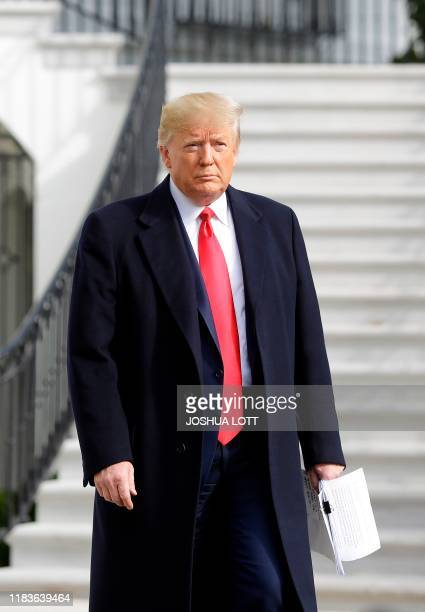 US President Donald Trump holds his notes as he talks to the media on the South Lawn of the White House before boarding Marine One in Washington DC...