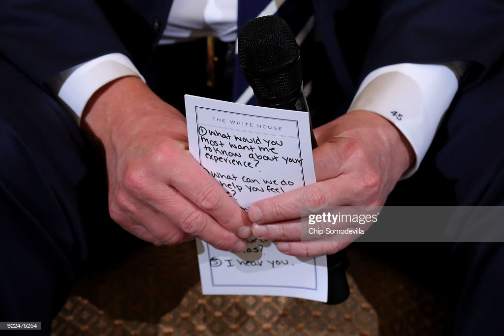 U.S. President Donald Trump holds his notes while hosting a listening session with students survivors of mass shootings, their parents and teachers in the State Dining Room at the White House February 21, 2018 in Washington, DC. Trump is hosting the session in the wake of last week's mass shooting at Marjory Stoneman Douglas High School in Parkland, Florida, that left 17 students and teachers dead.