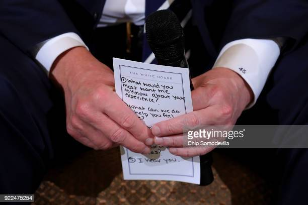 US President Donald Trump holds his notes while hosting a listening session with students survivors of mass shootings their parents and teachers in...