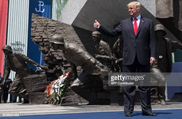 US President Donald Trump holds his thumb up as he stands in front of the Warsaw Uprising Monument on Krasinski Square during the Three Seas...