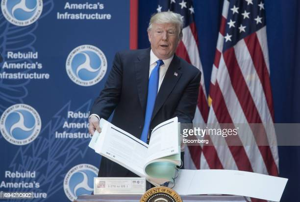 US President Donald Trump holds out a book containing environmental impact statements for a road during an event on infrastructure investment and...
