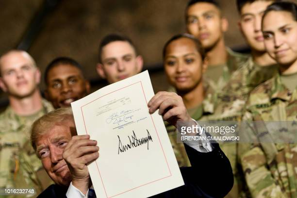 US President Donald Trump holds the John S McCain National Defense Authorization Act for Fiscal Year 2019 after signing it at Fort Drum New York on...