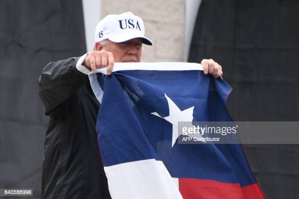 US President Donald Trump holds the state flag of Texas outside of the Annaville Fire House after attending a briefing on Hurricane Harvey in Corpus...