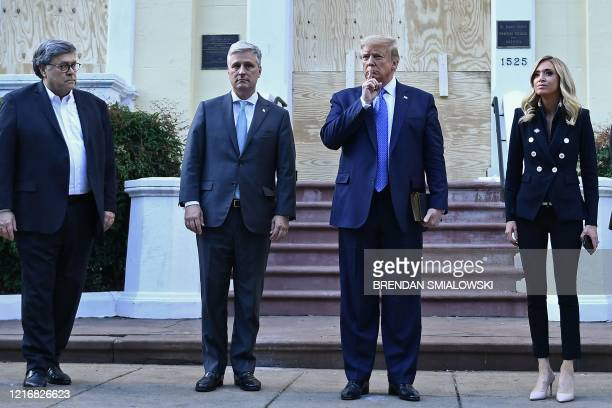 President Donald Trump holds up a Bible as he gestures alongside US Attorney General William Barr White House national security adviser Robert...
