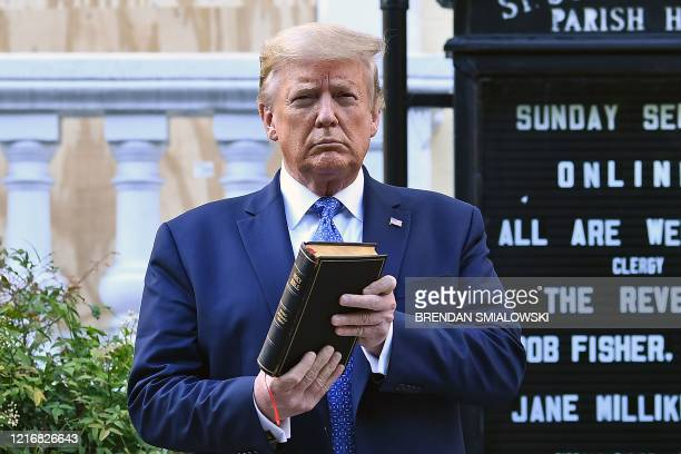 President Donald Trump holds up a Bible outside of St John's Episcopal church across Lafayette Park in Washington, DC on June 1, 2020. - US President...
