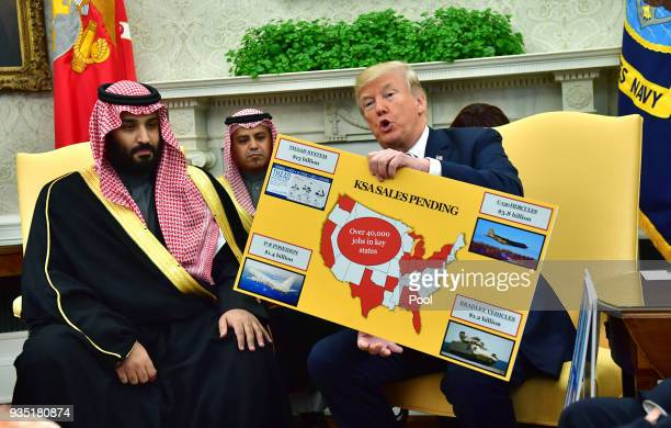 President Donald Trump holds up a chart of military hardware sales as he meets with Crown Prince Mohammed bin Salman of the Kingdom of Saudi Arabia...