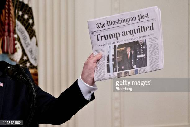 US President Donald Trump holds up a copy of the Washington Post newspaper during an event at the White House in Washington DC US on Thursday Feb 6...