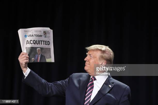 """President Donald Trump holds up a copy of USA Today newspaper with a banner headline that reads """"Acquitted"""" as he arrives to annual National Prayer..."""