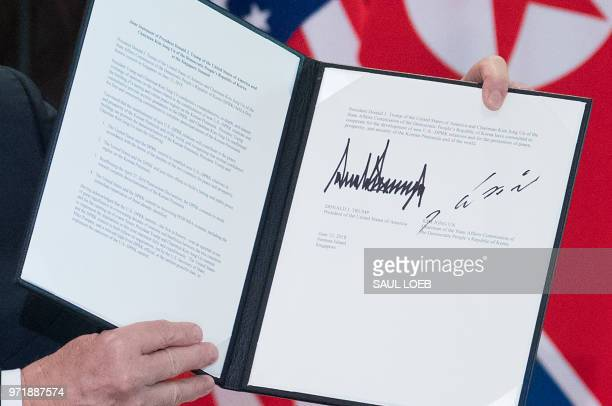President Donald Trump holds up a document signed by him and North Korea's leader Kim Jong Un following a signing ceremony during their historic...