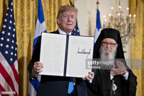 US President Donald Trump holds up a Greek Independence Day proclamation after being signed next to Archbishop Demetrios of America elder archbishop...