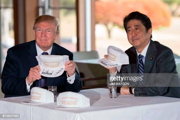US President Donald Trump holds up a hat with Japan's Prime Minister Shinzo Abe during a luncheon at the Kasumigaseki Country Club Golf Course in...