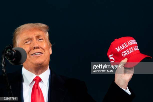 President Donald Trump holds up a MAGA hat as he speaks during a Make America Great Again campaign event at Des Moines International Airport in Des...