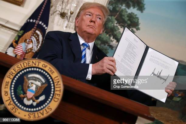 President Donald Trump holds up a memorandum that reinstates sanctions on Iran after he announced his decision to withdraw the United States from the...