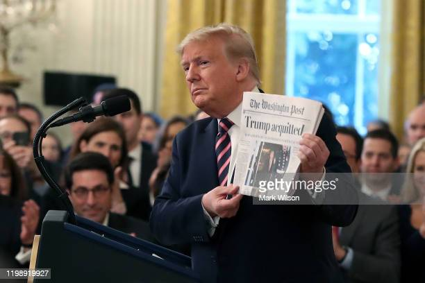 President Donald Trump holds up a newspaper as he speaks one day after the U.S. Senate acquitted on two articles of impeachment, in the East Room of...