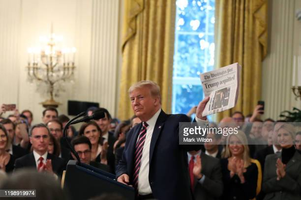 S President Donald Trump holds up a newspaper as he speaks one day after the US Senate acquitted on two articles of impeachment in the East Room of...