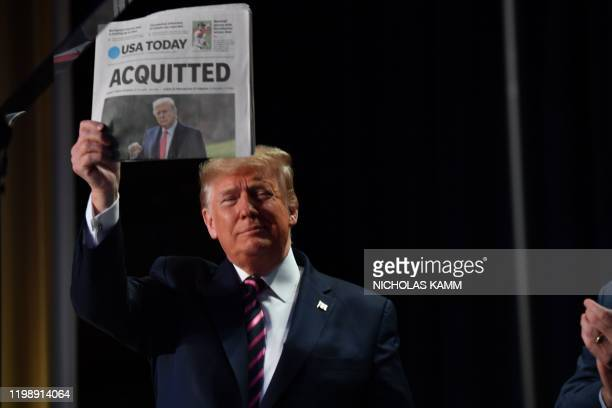 US President Donald Trump holds up a newspaper that displays a headline Acquitted as he arrives to speak at the 68th annual National Prayer Breakfast...