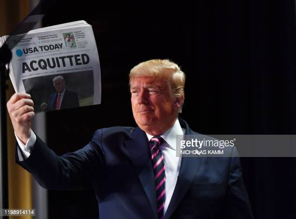 """President Donald Trump holds up a newspaper that displays a headline """"Acquitted"""" as he arrives to speak at the 68th annual National Prayer Breakfast..."""