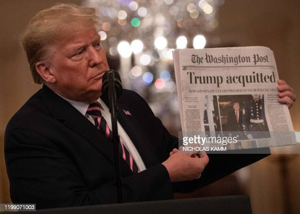 """President Donald Trump holds up a newspaper that displays a headline """"Acquitted"""" while speaking about his Senate impeachment trial in the East Room..."""
