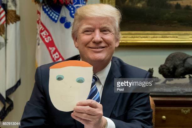 President Donald Trump holds up a note and drawing depicting him that was created by the child of Greg Knox of Ohio during a meeting on healthcare in...