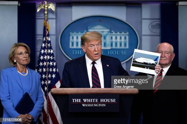 S President Donald Trump holds up a picture of a Boeing 747 Dreamlifter as Secretary of Education Betsy DeVos and Secretary of Agriculture Sonny...