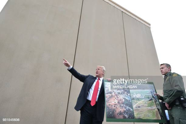 US President Donald Trump holds up a poster of before and after photos of a segment of the border wall prototypes with Chief Patrol Agent Rodney S...