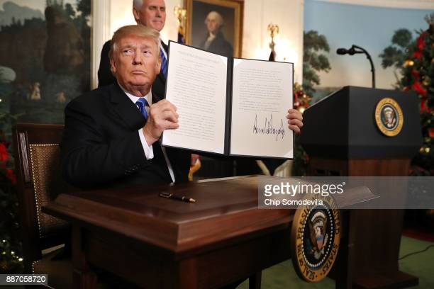 President Donald Trump holds up a proclaimation that the U.S. Government will formally recognize Jerusalem as the capital of Israel after signing the...