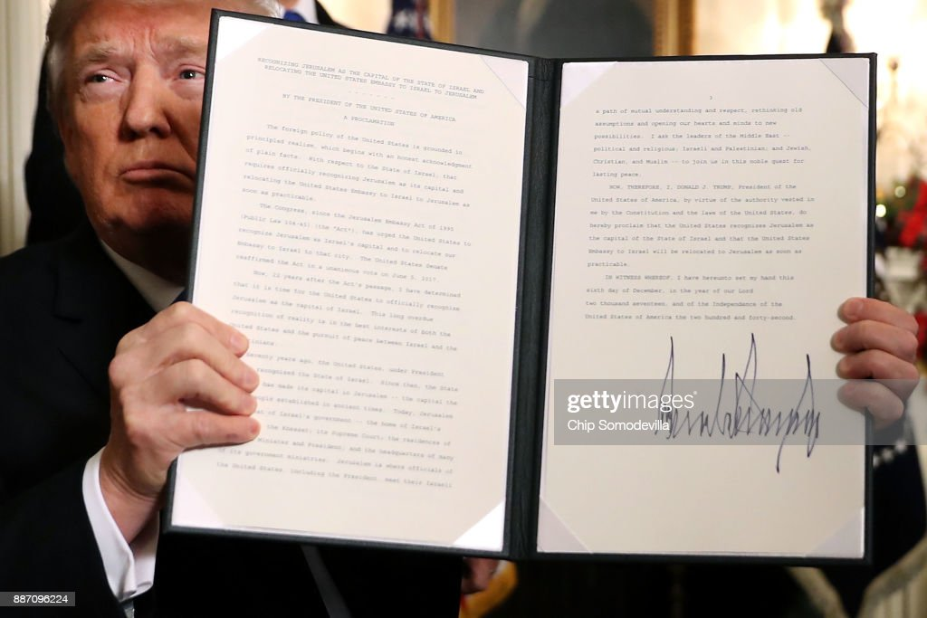 U.S. President Donald Trump holds up a proclaimation that the U.S. government will formally recognize Jerusalem as the capital of Israel after signing the document in the Diplomatic Reception Room at the White House December 6, 2017 in Washington, DC. In keeping with a campaign promise, Trump said the United States will move its embassy from Tel Aviv to Jerusalem sometime in the next few years. No other country has its embassy in Jerusalem.