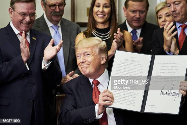 US President Donald Trump holds up a signed executive order on health care in the Roosevelt Room of the White House in Washington DC US on Thursday...