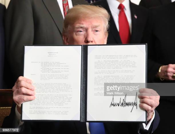 President Donald Trump holds up a signed presidential memorandum aimed at what he calls Chinese economic aggression in the Roosevelt Room at the...