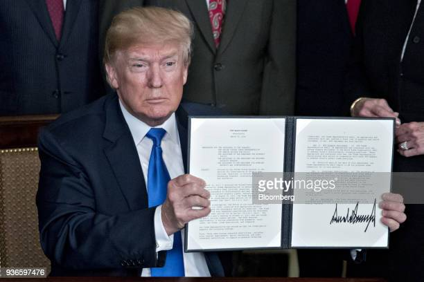 US President Donald Trump holds up a signed presidential memorandum targeting China's economic aggression in the Diplomatic Room of the White House...