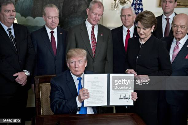 US President Donald Trump holds up a signed presidential memorandum targeting China's economic aggression surrounded by business leaders and cabinet...