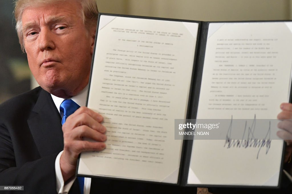 US President Donald Trump holds up a signed proclamation after he delivered a statement on Jerusalem from the Diplomatic Reception Room of the White House in Washington, DC on December 6, 2017. President Donald Trump on Wednesday recognized the disputed city of Jerusalem as Israel's capital -- a historic decision that overturns decades of US policy and risks triggering a fresh spasm of violence in the Middle East.'I have determined that it is time to officially recognize Jerusalem as the capital of Israel,' Trump said from the White House.'It's the right thing to do.' NGAN