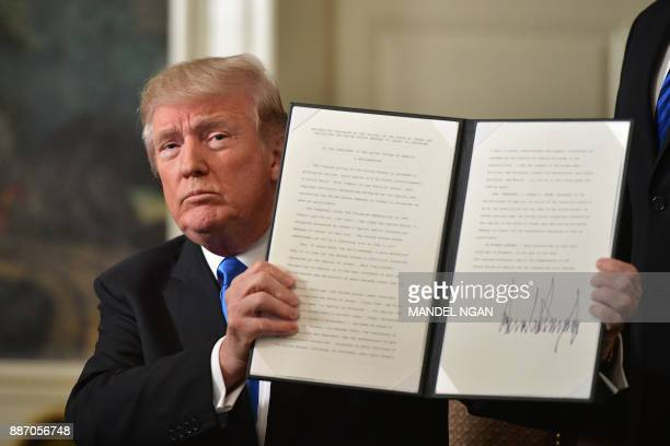 US President Donald Trump holds up a signed proclamation after he delivered a statement on Jerusalem from the Diplomatic Reception Room of the White...