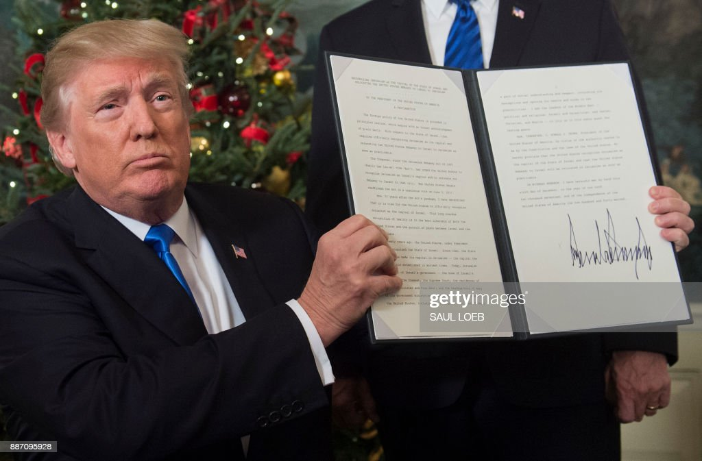 President Donald Trump holds up a signed proclamation after he delivered a statement on Jerusalem from the Diplomatic Reception Room of the White House in Washington, DC on December 6, 2017. President Donald Trump on Wednesday recognized the disputed city of Jerusalem as Israel's capital -- a historic decision that overturns decades of US policy and risks triggering a fresh spasm of violence in the Middle East.'I have determined that it is time to officially recognize Jerusalem as the capital of Israel,' Trump said from the White House.'It's the right thing to do.' /