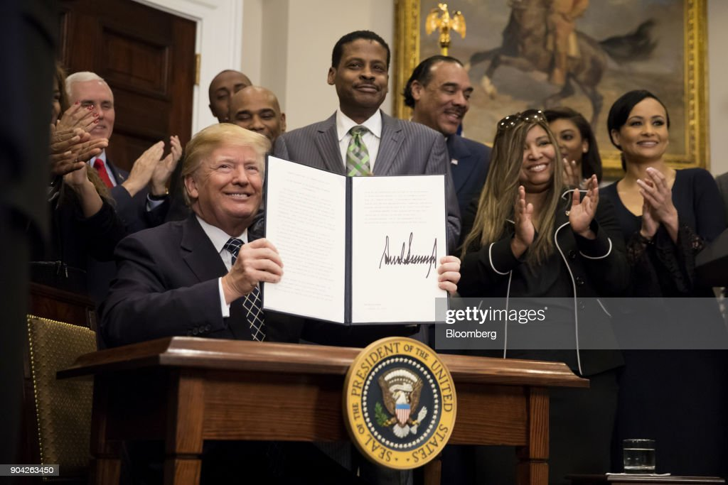 U.S. President Donald Trump holds up a signed proclamation for Martin Luther King Jr. Day in the Roosevelt Room of the White House in Washington, D.C., U.S., on Friday, Jan. 12, 2018. Trump blew up negotiations on a potential immigration deal, pushing both sides to harden their positions and raising the risks that the standoff will sink talks aimed at averting a government shutdown at the end of next week. Photographer: Eric Thayer/Bloomberg via Getty Images