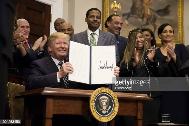 US President Donald Trump holds up a signed proclamation for Martin Luther King Jr Day in the Roosevelt Room of the White House in Washington DC US...