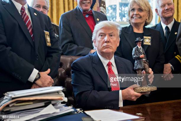 US President Donald Trump holds up a statue he received as a gift while meeting with county sheriffs in the Oval Office of the White House on...