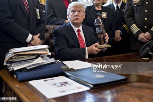 US President Donald Trump holds up a statue he received as a gift while meeting with county sheriffs in the Oval Office of the White House in...