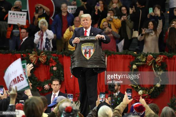 S President Donald Trump holds up a vest given to him to autograph during a rally at the Pensacola Bay Center on December 8 2017 in Pensacola Florida...